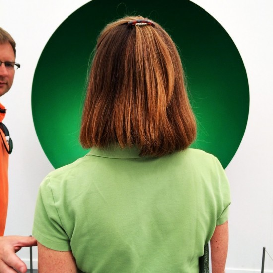 Woman with green shirt in front of an Anish Kapoor work
